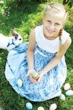 Dziecko z białym królika gmeraniem dla kolorowych jajek na łące Obrazy Royalty Free