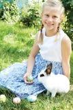 Dziecko z białym królika gmeraniem dla kolorowych jajek na łące Zdjęcia Royalty Free