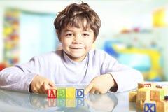 Dziecko z drewnianymi sześcianami Obrazy Royalty Free
