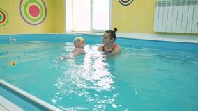 Dziecko z instruktora uczenie pływać w basenie zbiory wideo