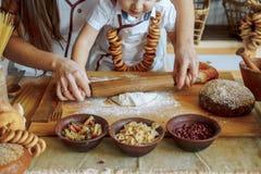 Dziecko z jego matką w kuchennych promocjach ciasto, produkty od ciasta, mąka, piekarnia, chleb Mistrzowska klasa zdjęcia stock