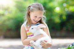 Dziecko z królikiem Wielkanoc królik Dzieciaki i zwierzęta domowe Zdjęcia Stock