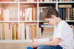 Dziecko z książką w bibliotece zdjęcia stock