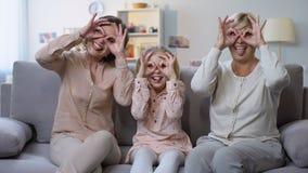 Dziecko z matką i babcią robi śmiesznym twarzom, gestykuluje gogle rękami, zabawa zbiory