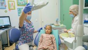 Dziecko z matką przy dentysty ` s przyjęciem Dziewczyna kłama w krześle za jej matką, Lekarek pracy z zdjęcia stock