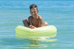 Dziecko z nadmuchiwanym pierścionkiem w morzu obrazy royalty free