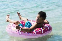 Dziecko z nadmuchiwanym pierścionkiem w morzu zdjęcia stock