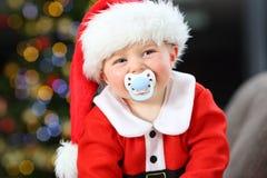 Dziecko z pacyfikatorem patrzeje kamerę w bożych narodzeniach zdjęcie royalty free