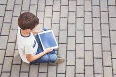 Dziecko z pastylki komputerowym obsiadaniem outdoors Edukacja, uczenie, technologia, przyjaciele, szkolny pojęcie Odgórny widok Zdjęcie Royalty Free