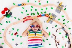 Dziecko z zabawka pociągiem Żartuje drewnianą kolej zdjęcie royalty free