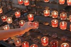 Dziecko zaświeca czerwoną świeczkę w kościół i wtedy mówi modlitwę dla th Zdjęcie Royalty Free