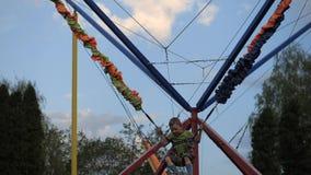 Dziecko zabawę na boisku chłopiec skacze na trampoline w parku rozrywki Dzieci zrozumienia na zbawczych arkanach zbiory