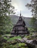 Dziejowy Borgund klepki kościół w Norwegia z otaczającym cmentarzem i obramiającym drzewami zdjęcia royalty free