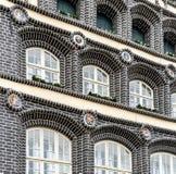 Dziejowy budynek z czarnymi dekoracjami na façade i cegłami fotografia royalty free