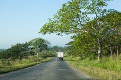 Dzielnicowa droga w Kuba z zielonymi drzewami wokoło Zdjęcia Royalty Free