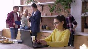 Dzienna biurowa praca, biznesowa kobieta jest ubranym szkła pracuje na laptopie podczas gdy koledzy jedzą fast food i komunikują  zbiory