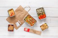 Dzienni posiłki doręczeniowi w foliowych zbiorników odgórnym widoku na białym drewnie Zdjęcie Royalty Free