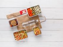 Dzienni posiłki doręczeniowi w foliowych zbiorników odgórnym widoku na białym drewnie Fotografia Royalty Free