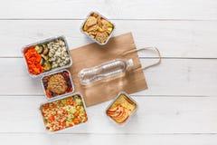 Dzienni posiłki doręczeniowi w foliowych zbiorników odgórnym widoku na białym drewnie Fotografia Stock