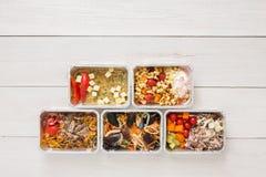 Dzienni posiłki doręczeniowi w foliowych zbiorników odgórnym widoku na białym drewnie Obrazy Royalty Free