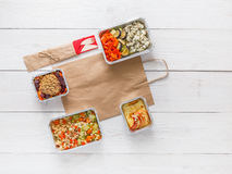 Dzienni posiłki doręczeniowi w foliowych zbiorników odgórnym widoku na białym drewnie Zdjęcia Royalty Free