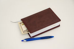 Dzienniczek pióro i niektóre dolary, Obrazy Royalty Free