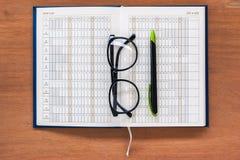 Dzienniczka planisty książki otwarta kalendarzowa strona z szkłami i piórem Fotografia Stock