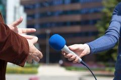 Dziennikarz przeprowadza wywiad biznesmena, korporacyjny budynek w tle fotografia royalty free