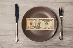 Dziesięć Amerykańskich dolarów rachunku na brawn talerzu z rozwidleniem i nożem Mo Fotografia Stock