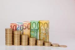 Dziesięć, dwadzieścia, pięćdziesiąt, sto, dwieście i moneta euro staczający się, wystawiają rachunek banknoty na białym tle Histo obrazy royalty free