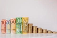 Dziesięć, dwadzieścia, pięćdziesiąt, sto, dwieście i moneta euro staczający się, wystawiają rachunek banknoty na białym tle Histo zdjęcia stock