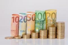 Dziesięć, dwadzieścia, pięćdziesiąt, sto, dwieście i moneta euro staczający się, wystawiają rachunek banknoty na białym tle Histo obraz royalty free