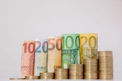 Dziesięć, dwadzieścia, pięćdziesiąt, sto, dwieście i moneta euro staczający się, wystawiają rachunek banknoty na białym tle Histo zdjęcie royalty free