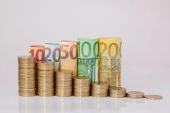Dziesięć, dwadzieścia, pięćdziesiąt, sto, dwieście i moneta euro staczający się, wystawiają rachunek banknoty na białym tle Histo fotografia royalty free