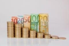 Dziesięć, dwadzieścia, pięćdziesiąt, sto, dwieście i moneta euro staczający się, wystawiają rachunek banknoty na białym tle Histo fotografia stock