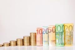 Dziesięć, dwadzieścia, pięćdziesiąt, sto, dwieście i moneta euro staczający się, wystawiają rachunek banknoty na białym tle Histo obrazy stock