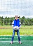 Dziesięć lat dziewczyny stojaków w futbolowej bramie jako bramkarz i chwyty piłka zdjęcia stock
