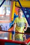 Dziesięć lat szczęśliwi i uśmiechniętej chłopiec bawić się lotniczego hokeja na dziecko gier pokoju Zdjęcia Royalty Free