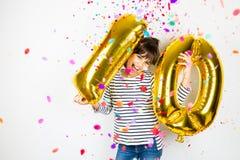 Dziesięć przyjęć urodzinowych dziewczyna z złotymi balonami i confetti zdjęcie stock