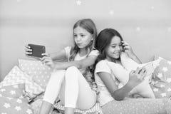 Dziewczęcy czas wolny piżamy przyjęcie Dziewczyny smartphone mali bloggers Online rozrywka Bada ogólnospołeczną sieć Smartphone zdjęcie royalty free
