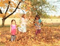 Dziewczyn bawić się bosy z spadać liśćmi Zdjęcia Royalty Free