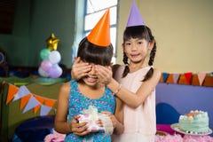 Dziewczyn dziewczyn nakrywkowi urodzinowi oczy i ofiara prezent Zdjęcie Stock