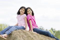 dziewczyn haybale obsiadania wierzchołka dwa potomstwa fotografia stock