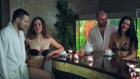 Dziewczyn i chłopiec pić herbaciany przy akwarium tłem i relaksować w sauna zbiory