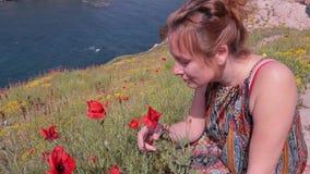 Dziewczyn kichnięcia ponieważ obwąchuje kwiaty maczek alergia zbiory