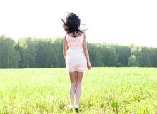 Dziewczyn menchii suknia jest skokowym łąkowym latem, szczęścia pojęcia zabawa pomysł, relaks postaci słońca radość Obrazy Stock