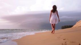 Dziewczyn nogi chodzi plażowego zmierzchu morze zbiory