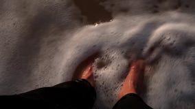 Dziewczyn nogi w czarnych cajgach na mokrym piasku z skorup obmyciami surfują, machają z pianą, zbiory wideo