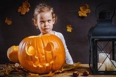 Dziewczyn pozy z Halloweenową banią Obrazy Royalty Free