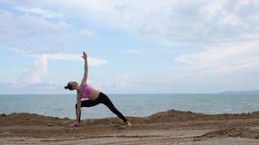 Dziewczyn praktyk joga sprawności fizycznej ćwiczenie blisko ocean plaży w wojownik pozie zbiory